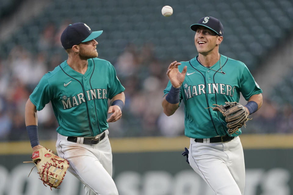 Seattle Mariners first baseman Jake Bauers, left, tosses the ball to second baseman Dylan Moore after Bauers caught a pop-up hit by Tampa Bay Rays' Randy Arozarena to end the top of the fifth inning of a baseball game, Friday, June 18, 2021, in Seattle. (AP Photo/Ted S. Warren)