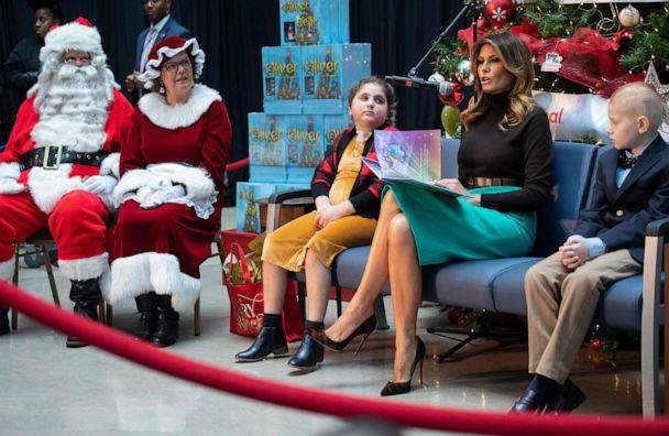 PHOTO: First lady Melania Trump reads the book, 'Oliver the Ornament Meets Belle', alongside patients Sammie Burley and Declan McCahan, during a visit to Children's National Hospital in Washington, Dec. 6, 2019. (Saul Loeb/AFP via Getty Images)