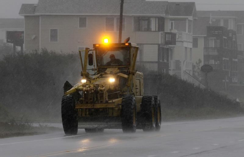 Earth moving equipment drives south along Virginia Dare Trail in the rain and wind generated by Hurricane Sandy in Kill Devil Hills, N.C., Sunday, Oct. 28, 2012 as The storm moves up the east coast. Tens of thousands of people were ordered to evacuate coastal areas Sunday as big cities and small towns across the U.S. Northeast braced for the onslaught of a superstorm threatening some 60 million people along the most heavily populated corridor in the nation. (AP Photo/Gerry Broome)