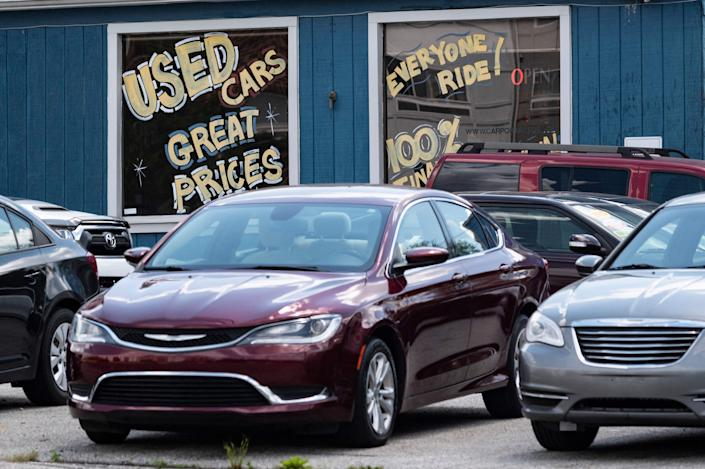 Cars sit outside a used car dealership with spray paint on the windows advertising the vehicles.