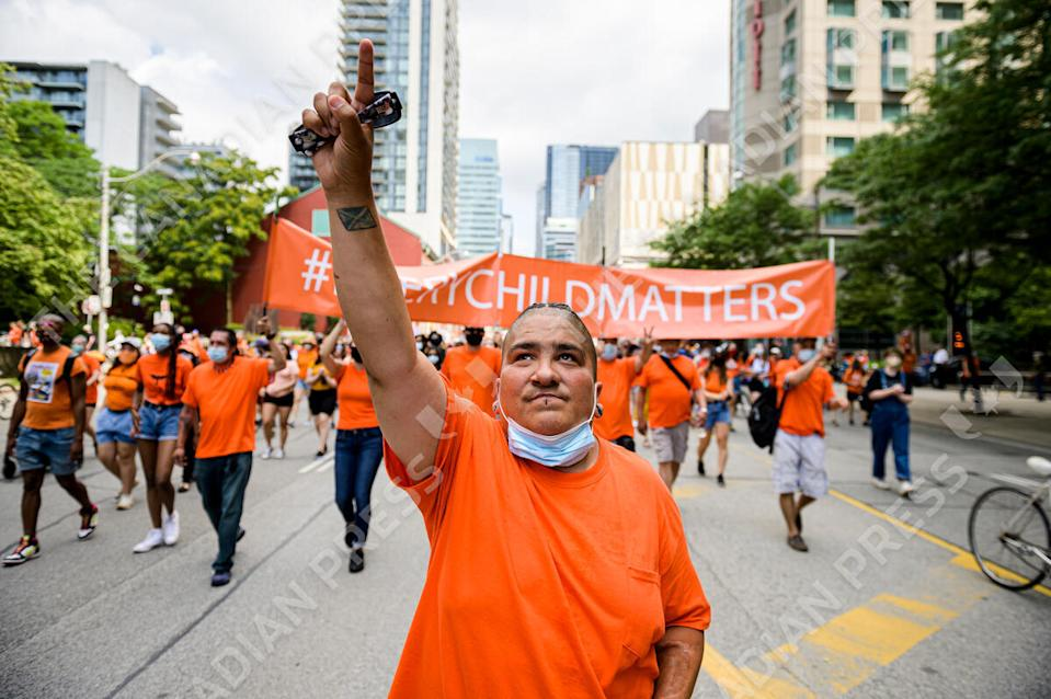 <p>Demonstrators participate in the Every Child Matters Walk on Canada Day, in downtown Toronto, on Thursday, July 1, 2021. THE CANADIAN PRESS/Christopher Katsarov</p>