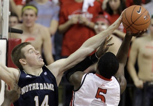 Notre Dame's Scott Martin (14) makes a block on a shot by Rutgers' Eli Carter (5) during the first half of an NCAA college basketball game Monday, Jan. 16, 2012, in Piscataway, N.J. (AP Photo/Julio Cortez)