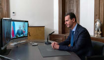 FILE - In this November 9, 2020 file photo, released by the Syrian official news agency SANA, Syrian President Bashar Assad listens to Russian President Vladimir Putin during their talks via video conference, in Damascus, Syria. On Nov. 13, 1970, Hafez Assad a young career air force officer launched a bloodless coup. Fifty years later, Assad's family still rules Syria. The country is in ruins from a decade of civil war that killed around a half million people, displaced half the population and virtually wiped out the economy. But Hafez's son, Bashar Assad, has an unquestioned grip on what remains. (SANA via AP, File)
