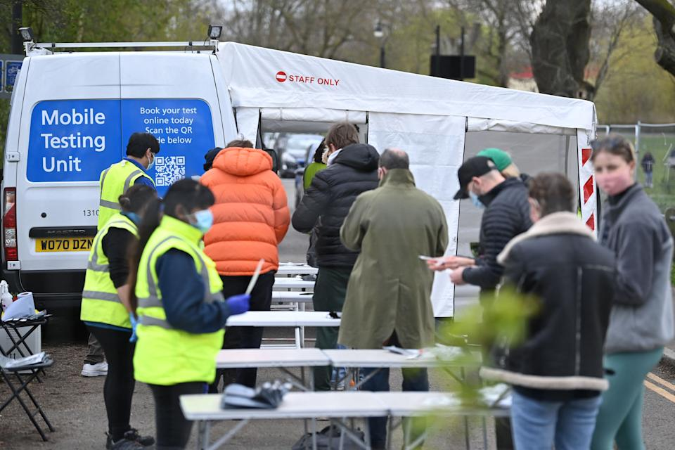 People check their paper-work as they queue to take a Covid-19 test at a mobile novel coronavirus testing centre on Clapham Common in south London, on April 13, 2021. - Britain said late Monday it had hit a target to offer a coronavirus vaccine first dose to all over-50s by mid-April, as England's lockdown-weary population toasted a significant easing of restrictions with early morning pints and much-needed haircuts. (Photo by DANIEL LEAL-OLIVAS / AFP) (Photo by DANIEL LEAL-OLIVAS/AFP via Getty Images)