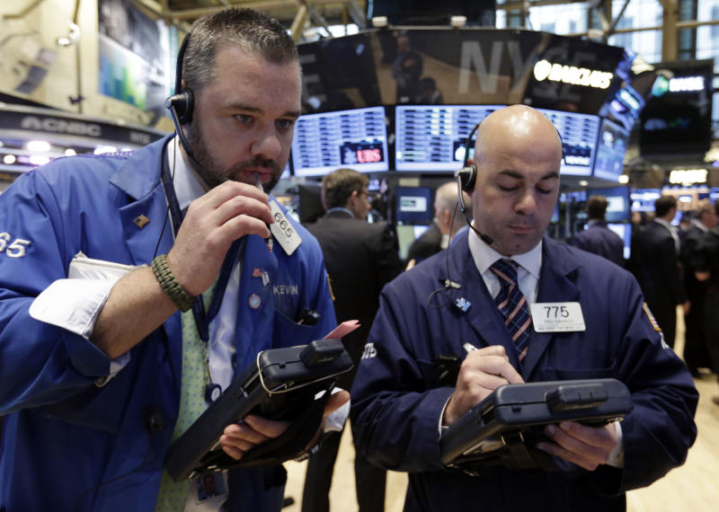 Traders Kevin Lodewick, left, and Fred DeMarco work on the floor of the New York Stock Exchange Tuesday, June 11, 2013. Stocks are falling in early trading on Wall Street, following global markets lower after the Bank of Japan declined to take further action to shore up that country's financial system. (AP Photo/Richard Drew)