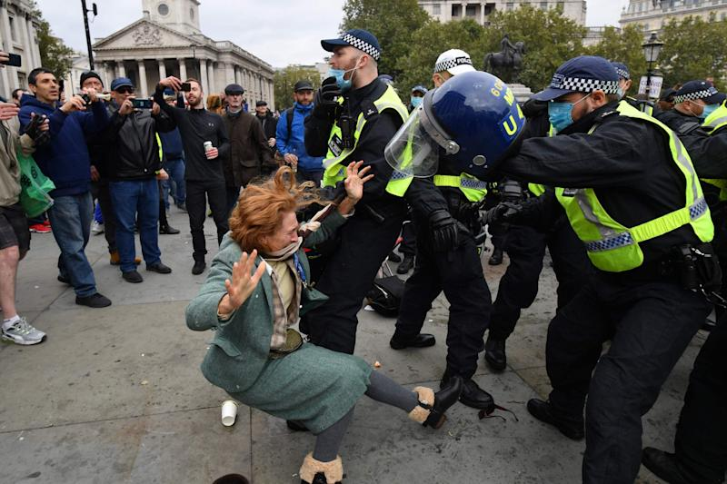 A woman falls to the ground as police try to break up the rally (AFP via Getty Images)