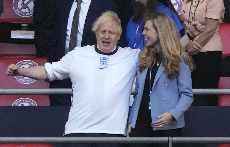 UK Prime Minister Boris Johnson (L) and his spouse Carrie arrive before the start of the UEFA EURO 2020 semi-final football match between England and Denmark at Wembley Stadium in London on July 7, 2021. (Photo by Frank Augstein / POOL / AFP) (Photo by FRANK AUGSTEIN/POOL/AFP via Getty Images)