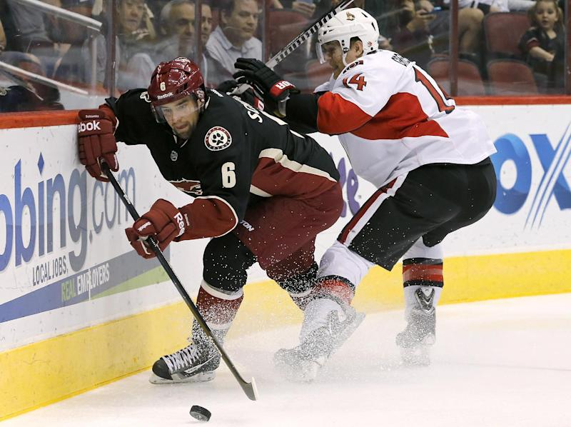 Phoenix Coyotes' David Schlemko (6) tries to keep the puck away from Ottawa Senators' Colin Greening (14) during the first period in an NHL hockey game Tuesday, Oct. 15, 2013, in Glendale, Ariz. (AP Photo/Ross D. Franklin)