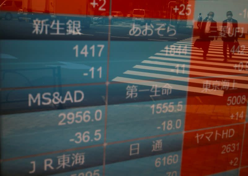 Passersby wearing protective face masks are reflected on a stock quotation board outside a brokerage, amid the coronavirus disease (COVID-19) outbreak, in Tokyo