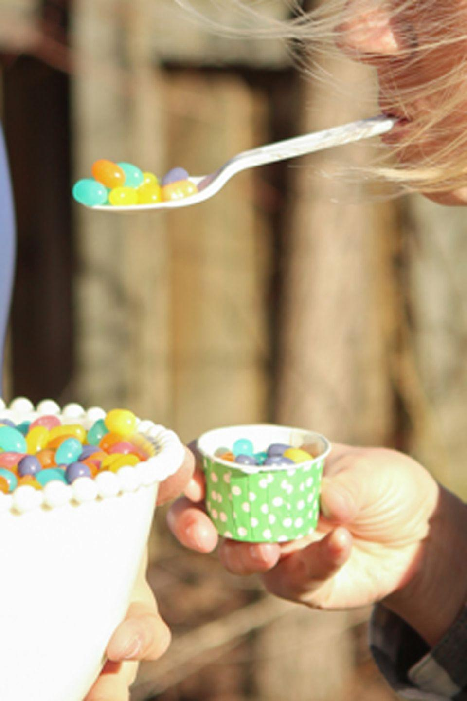 """<p>This game is like an egg and spoon race, but with Easter candy. Prep a bowl full of jelly beans and divide kids into teams. Give each kid a spoon to hold in his or her mouth. Each team has to transfer the jelly beans from the bowl to a nearby cup. The first team to fill their cup wins!</p><p><em>Get the tutorial at <a href=""""http://www.playpartyplan.com/2015/04/12-fun-games-to-play-in-spring.html#_a5y_p=3605733"""" rel=""""nofollow noopener"""" target=""""_blank"""" data-ylk=""""slk:Play Party Plan"""" class=""""link rapid-noclick-resp"""">Play Party Plan</a>.</em></p>"""
