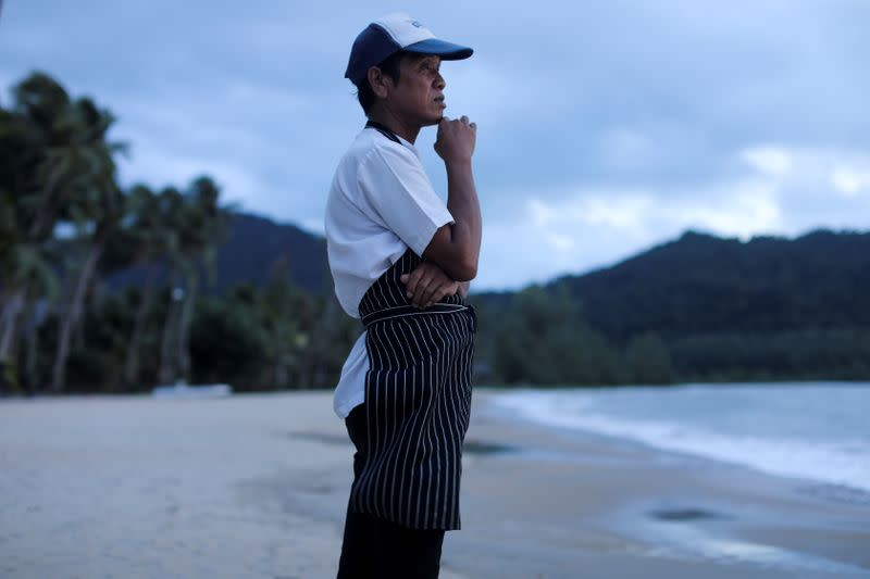 FILE PHOTO: A chef stands on an empty beach as he waits for the costumers at Koh Chang island in Thailand