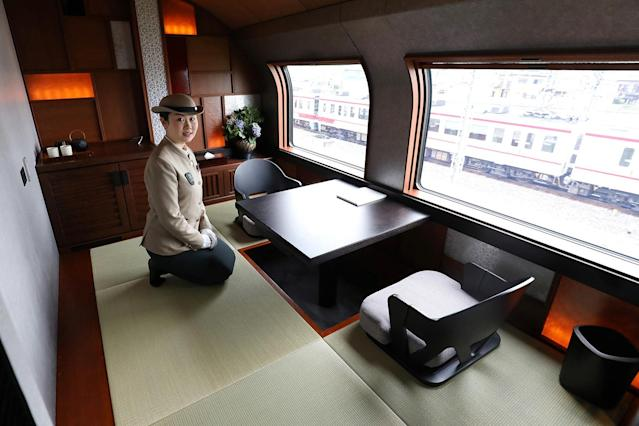 <p>A crew member kneels beside the dining set inside the Shiki-shima Suite, the top accomodation on the train, which comes at a cost of $10,000 per person for a four-day trip from Tokyo to Hokkaido. (Photo: STR/AFP/Getty Images) </p>