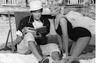 <p>James Stewart enjoys a beach read while spending time with actress Valerie Varda.</p>
