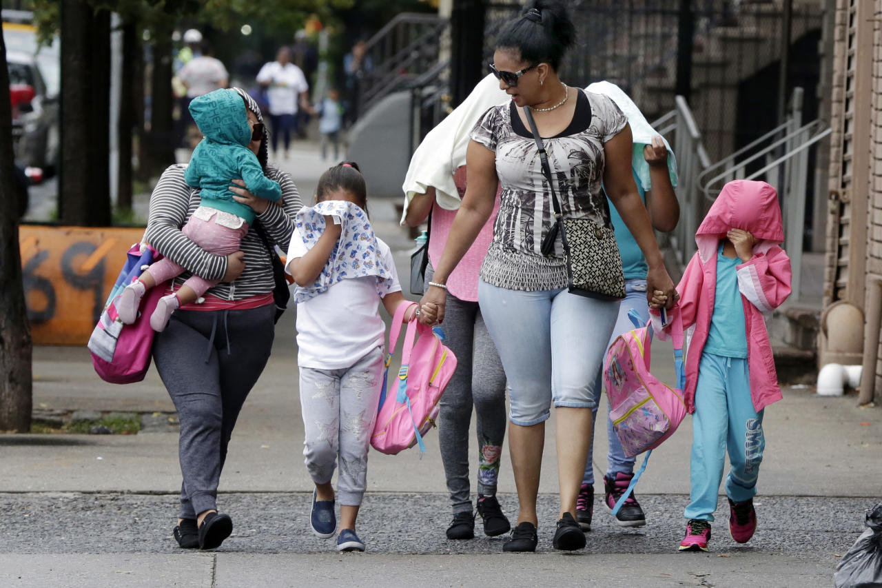 <p>Two woman accompany children to the Cayuga Centers in New York, Thursday, June 21, 2018. New York City Mayor Bill de Blasio says he learned on Wednesday that hundreds of migrant children separated from their parents by federal immigration officials are being cared for in the facility. (Photo: Richard Drew/AP) </p>