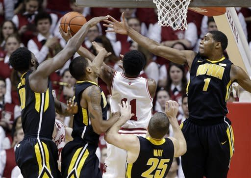 Indiana guard Kevin Ferrell (11) drives for a shot against Iowa players, left to right, Gabriel Olaseni, Roy Devyn Marble, Eric May, and Melsahn Basabe iduringthe first half of an NCAA college basketball game in Bloomington, Ind., Saturday, March 2, 2013. (AP Photo/Michael Conroy)