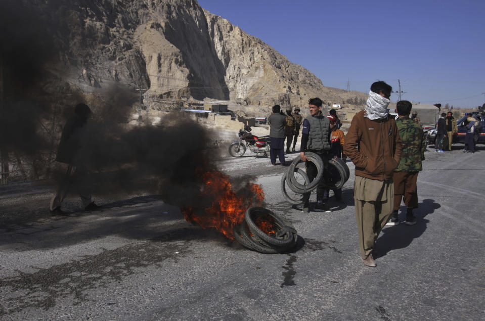 People from the Shiite Hazara community burn tires and block a road as a protest against the killing of coal mine workers by unknown gunmen near the Machh coal field, in Quetta, Pakistan, Sunday, Jan. 3, 2021. Gunmen opened fire on a group of minority Shiite Hazara coal miners after abducting them, killing 11 in southwestern Baluchistan province early Sunday, a Pakistani official said. (AP Photo/Arshad Butt)