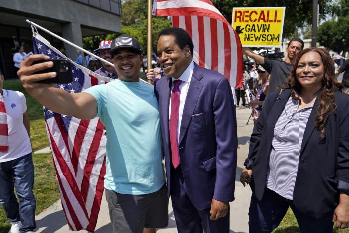 Radio talk show host Larry Elder, center, poses for selfies with supporters during a campaign stop Tuesday, July 13, 2021, in Norwalk, Calif. Elder announced Monday that he is running for governor of California. (AP Photo/Marcio Jose Sanchez)