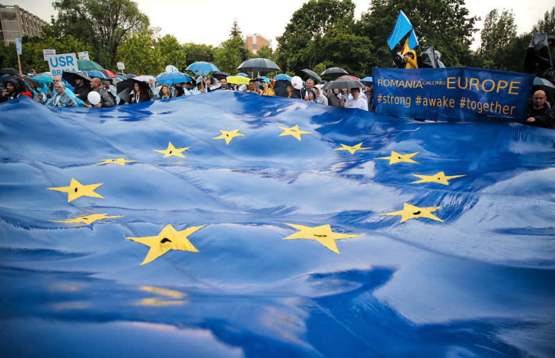 Romanians wave a large EU flag during a 2020 USR PLUS alliance European Parliament elections rally, in Bucharest, Romania, Friday, May 24, 2019. Romanians will vote on Sunday, May 26, in the European Parliament elections. (AP Photo/Vadim Ghirda)