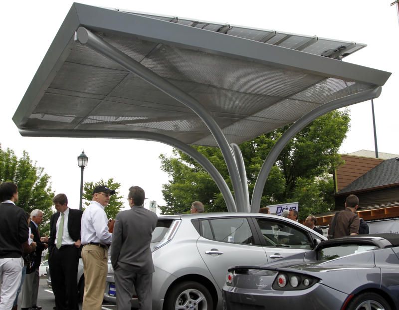 A solar canopy stands over Tesla, right, and Nissan Leaf electric cars at the unveiling of a solar-powered electric car charging station in Portland, Ore., Wednesday, June, 8, 2011. The grid-tied solar canopy, one of only two of its' kind in Portland, has two charging stations with the capacity to fully charge six electric vehicles a day.(AP Photo/Don Ryan)