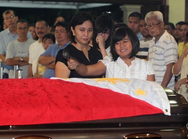 The wife of the late Interior and Local Government Secretary Jesse Robredo, Atty. Leni and daughters Aika, Patricia and Jillian sprinkle Holy Water to the remains of Robredo during the Holy Mass for the public viewing at the Archbishop's Palace in Naga City Tuesday night (August 21). President Benigno S. Aquino III signed Proclamation No. 460, declaring National Days of Mourning starting August 21 to mark the death of the former DILG Chief until his interment. The national flag will be flown at half-mast from sunrise to sunset in all government buildings in the Philippines and in the country's posts abroad for a period of six days.  (Ryan Lim, MPB, NPPA Images).
