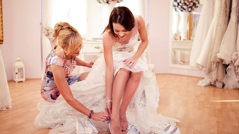 Bride adjusts wedding shoes in bridal gown as debate rages over controversial wedges