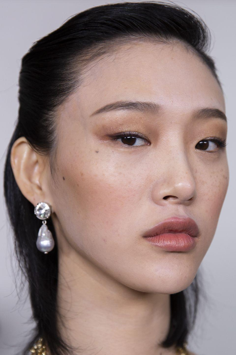 <p>Subtly bronzed cheeks with smokey copper eyelids and brown-toned lips make for a dreamy monochrome look.</p>