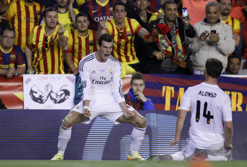 Real's Gareth Bale, left celebrates scoring his team's 2nd goal during the final of the Copa del Rey between FC Barcelona and Real Madrid at the Mestalla stadium in Valencia, Spain, Wednesday, April 16, 2014. (AP Photo/Alberto Saiz)