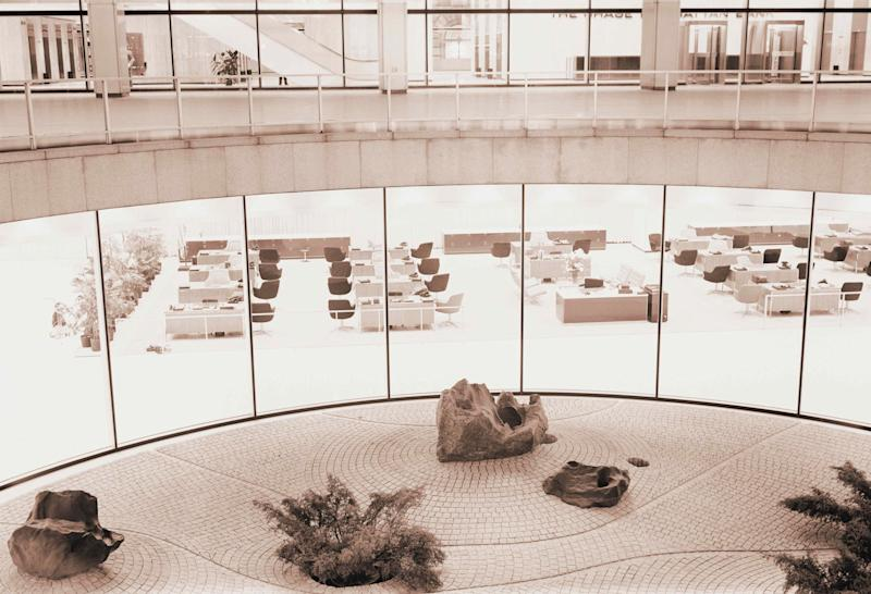 Rows of desks and chairs in an empty office surrounding an atrium rock garden, New York City.