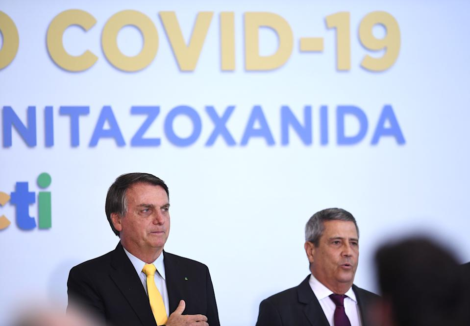 Brazilian President Jair Bolsonaro (L) and his Chief of Staff General Walter Souza Braga Netto attend an event to announce the clinical study of the use of Nitazoxanide in an early treatment against COVID-19, at Planalto Palace in Brasilia, on October 19, 2020. (Photo by EVARISTO SA / AFP) (Photo by EVARISTO SA/AFP via Getty Images)