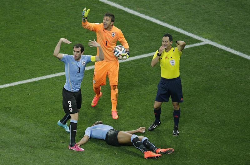 Uruguay's Diego Godin, goalkeeper Fernando Muslera and referee Carlos Velasco Carballo from Spain, from left, call for medical support as Uruguay's Alvaro Pereira lies on the floor during the group D World Cup soccer match between Uruguay and England at the Itaquerao Stadium in Sao Paulo, Brazil, Thursday, June 19, 2014