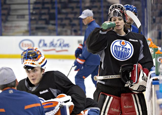 Canadian Olympic women's team goalie Shannon Szabados takes a water break during practice with the Edmonton Oilers NHL hockey team in Edmonton, Alberta, Wednesday, March 5, 2014. Oilers goaltender Ben Scrivens is at left facing the camera. (AP Photo/The Canadian Press, Jason Franson)
