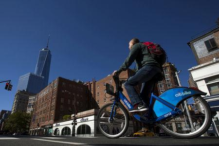 FILE PHOTO: A man rides a Citibike as he passes a Citibank ATM in the Manhattan borough of New York, October 10, 2015.  REUTERS/Eduardo Munoz/File Photo