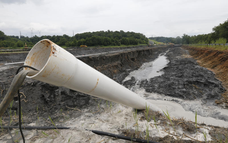 FILE - In this Friday June 26, 2015 file photo, a drain pipe sticks out of a coal ash retention pond at the Dominion Power's Possum Point Power Station in Dumfries, Va. The company is moving coal ash from several ponds to one lined pond. As Virginia and its public utilities struggle to cope with the coal ash buried in pits and ponds across the state, tons more of the industrial byproduct is being imported each year. (AP Photo/Steve Helber, File)