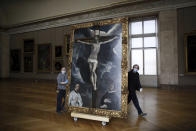 Workers at the Louvre museum transport a painting called 'Christ on the Cross Adored by Two Donors' by Spanish painter El Greco, as it returns from an exhibition at the Chicago Institute, in the Louvre museum, in Paris, Tuesday, Feb. 9, 2021. (AP Photo/Thibault Camus)