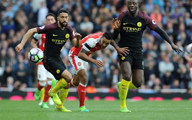 <span>Yaya Toure (right) knocks Theo Walcott off his stride</span> <span>Credit: GETTY IMAGES </span>