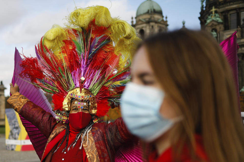 A man in a costume wears a face mask and dances as he attends a protest of people working in the entertainment and entertainment industry against the German government's economic policies to combat the spread of the coronavirus and COVID-19 disease and demand more support for their business, in Berlin, Germany, Wednesday, Oct. 28, 2020. (Photo/Markus Schreiber)