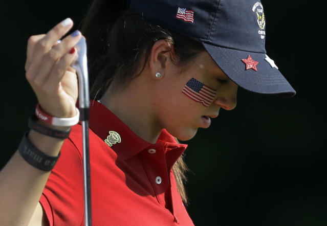 United States' Emma Talley looks down as she pulls a club out of her bag on the fifth fairway during the 38th Curtis Cup amateur golf match against Great Britain and Ireland Friday, June 6, 2014, in St. Louis. (AP Photo/Jeff Roberson)