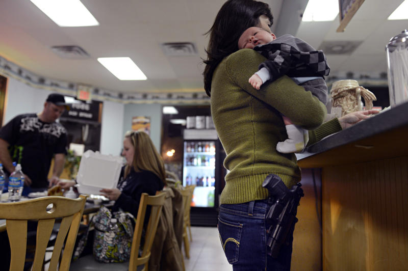 Denice Tarrant holds her two-week-old grandson Maxwell Reed as she pays for dinner at All Around Pizza in Virginia Beach, Va., on Monday, Feb. 18, 2013, where anyone who carries a gun or brings a concealed handgun permit is offered at 15 percent discount. (AP Photo/The Virginian-Pilot, Amanda Lucier) MAGS OUT