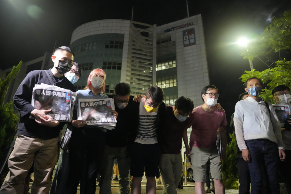 Reporters of Apple Daily bow to thank their supporters at the headquarters in Hong Kong, Thursday, June 24, 2021. Hong Kong's pro-democracy Apple Daily newspaper will stop publishing Thursday, following last week's arrest of five editors and executives and the freezing of $2.3 million in assets under the city's year-old national security law. (AP Photo/Kin Cheung)