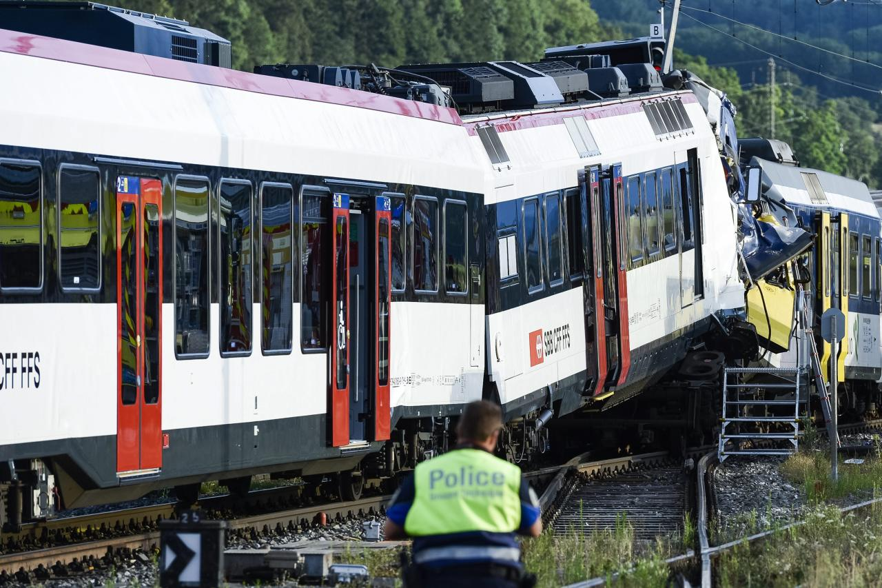 A police officer inspects the site where two passenger trains collided head-on in Granges-pres-Marnand, western Switzerland, Monday, July 29, 2013. Numerous people have been injured. (AP Photo/Keystone, Laurent Gillieron)