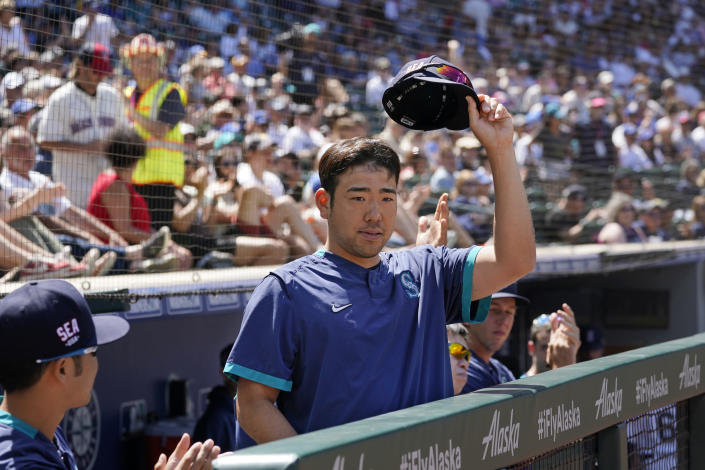 Seattle Mariners pitcher Yusei Kikuchi tips his cap to fans as a public address announcement is made that he was named to the American League All Star team, during a baseball game against the Texas Rangers, Sunday, July 4, 2021, in Seattle. (AP Photo/Elaine Thompson)