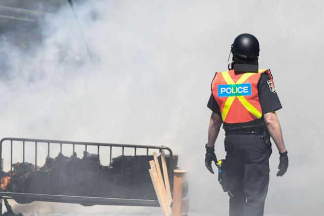 <p>Police walk past furniture set on fire by protesters during a demonstration in Quebec City on June 8, 2018, as the G7 Summits gets underway. (Photo: Martin Ouellet-Diotte/AFP/Getty Images) </p>