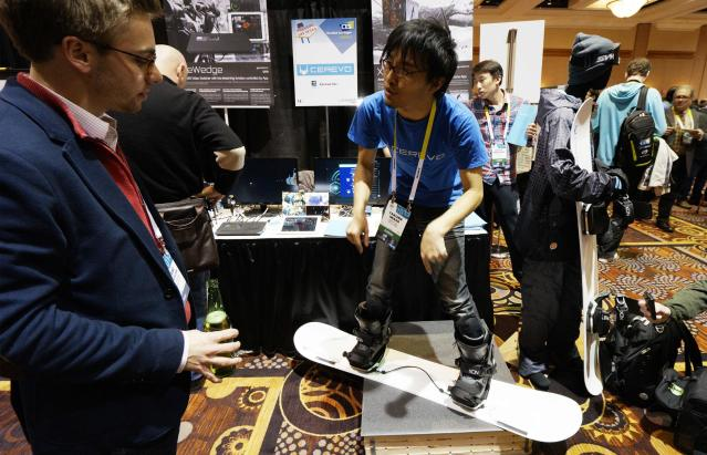 Takuma Iwasa (R) of Cerevo Inc. demonstrates the Xon Snow-1 snowboard analyzing system at the International Consumer Electronics show (CES) in Las Vegas, Nevada January 4, 2015. The Xon uses special bindings and a smartphone app to analyze a snowboarder's technique. REUTERS/Rick Wilking (UNITED STATES - Tags: BUSINESS SCIENCE TECHNOLOGY)