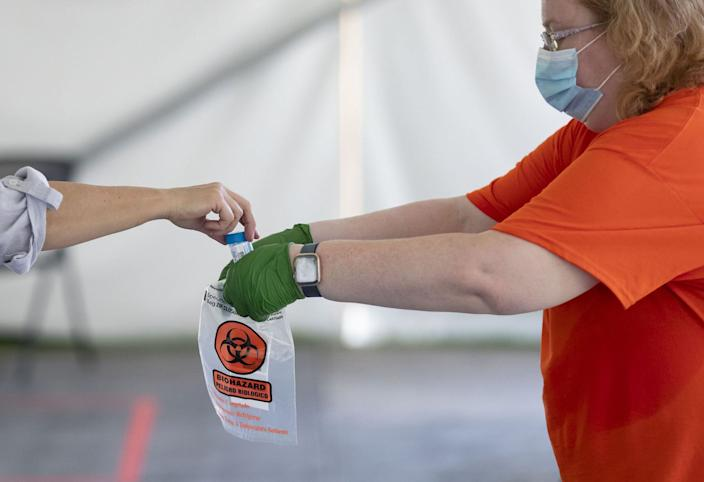 """A COVID-19 saliva sample is collected as testing is conducted on July 7, 2020, in a tent on the University of Illinois at Urbana-Champaign campus. <p class=""""copyright"""">Brian Cassella/Chicago Tribune/Getty Images</p>"""