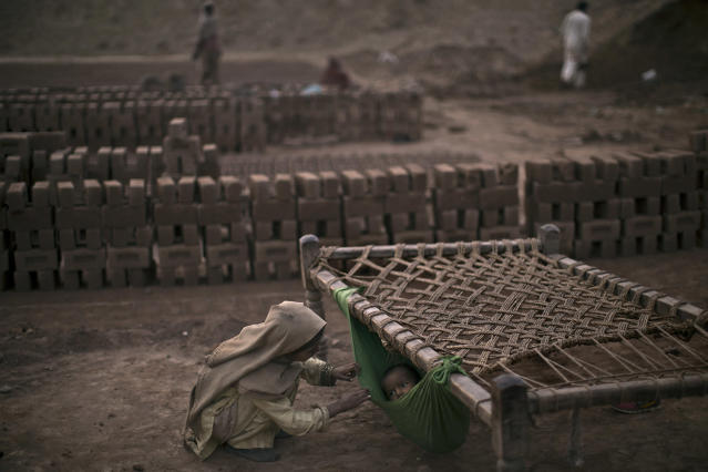 <p>Pakistani girl, Kiran Riasat, 8, who works with her mother and father, seen in the background, in a brick factory, checks on her brother, Rizwan, 1.5, laying in a hammock attached on a bed, at the site of work, in the outskirts of Islamabad, Pakistan, Feb. 18, 2014. (Photo: Muhammed Muheisen/AP) </p>