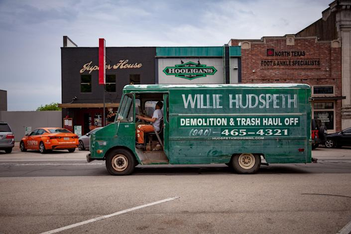 """The words """"Willie Hudspeth Demolition and Trash Haul Off"""" are painted on the side of a green truck."""