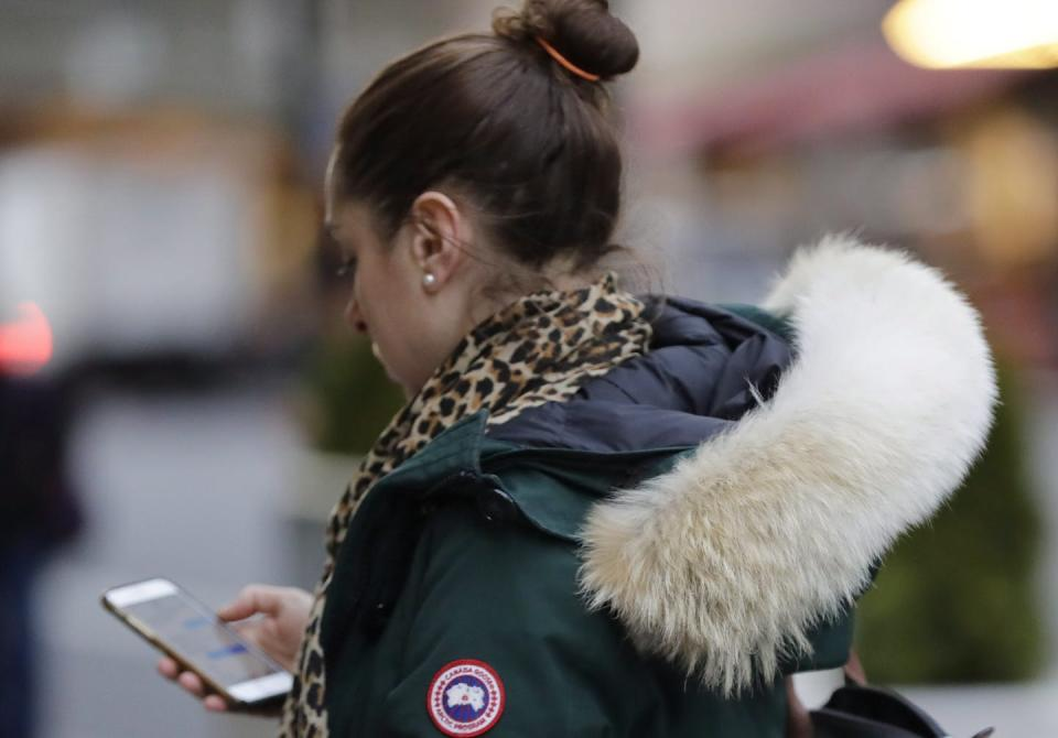 A woman looks at her phone as she walks along a street wearing a Canada Goose coat.