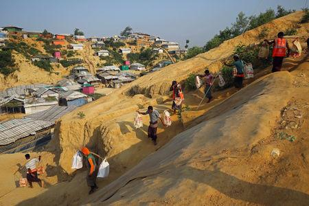 Rohingya refugees carry bricks to a construction site at the Balukhali camp in Cox's Bazar, Bangladesh, April 8, 2019. REUTERS/Mohammad Ponir Hossain