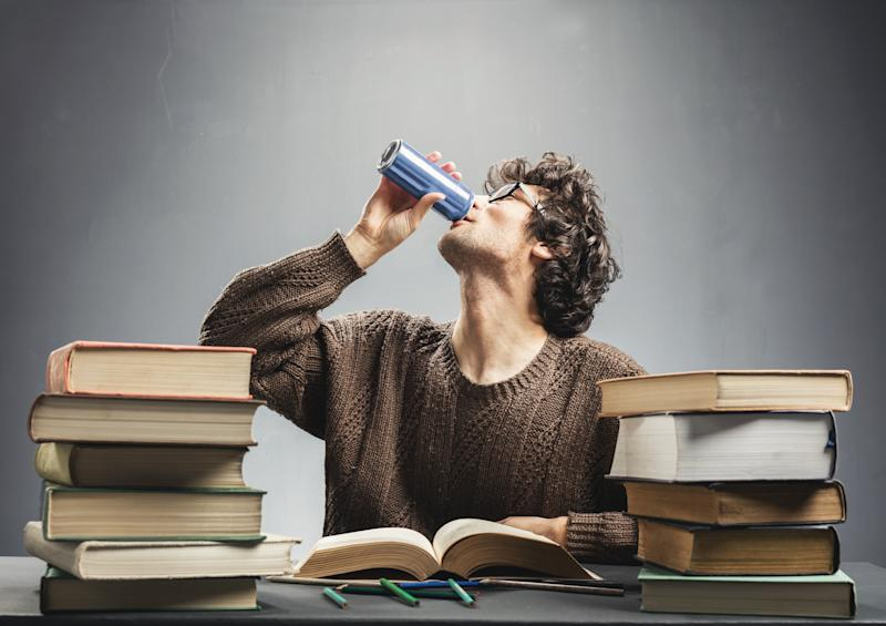 A young man guzzles a drink from a can while poring over a pile of books on a desk.