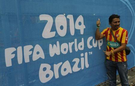 A soccer fan poses in front of a banner at the entrance to the Arena Baixada soccer stadium in Curitiba
